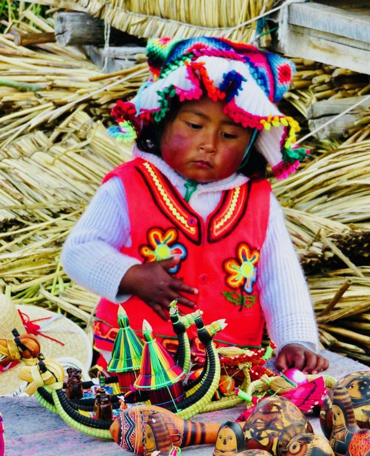 Little kid with traditional clothing at Islas Uros in Puno Peru, Travel blog Peru